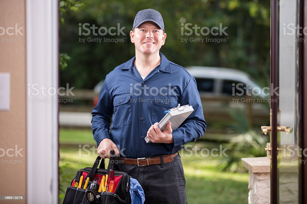 Service Industry: Repairman at customer's front door. stock photo