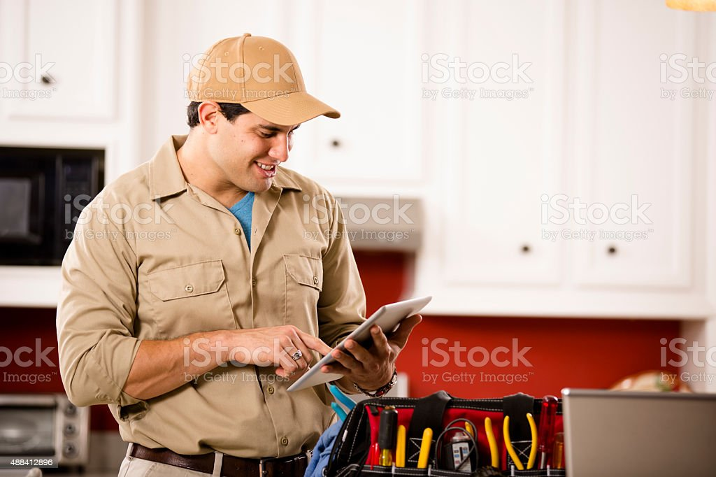 Service Industry:  Repairman working at customer's home. Tools. Digital tablet. stock photo