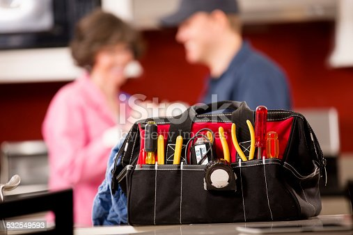 Close up of a bag filled with a repairman's tools in home kitchen. Caucasian repairmen or blue collar/service industry worker makes service/house call at customer's home.  He talks with customer in background. Inspector, exterminator, electrician, plumber, repairman.