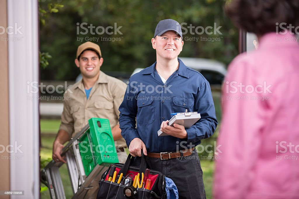 Service Industry Two Multiethnic Repairmen At Customers Front Door Stock Photo