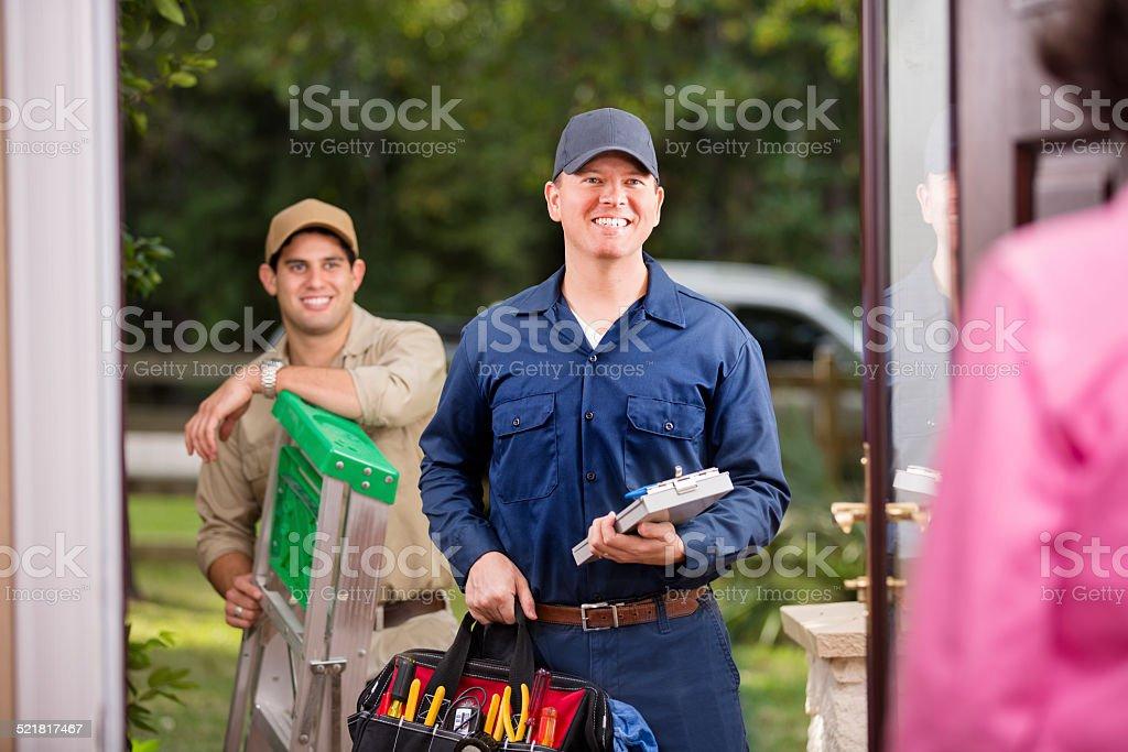 Service Industry: Two multi-ethnic repairmen at customer's front door. stock photo