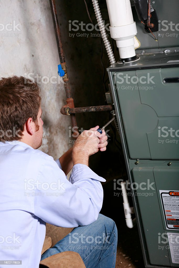 A service man working on a home furnace stock photo