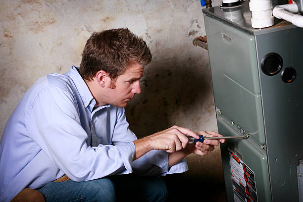 service man working on furnace - furnace stock photos and pictures