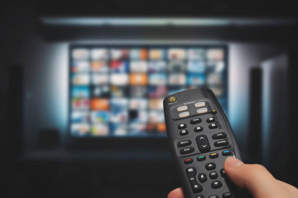 VOD service on television. TV streaming concept VOD service on television. Man watching TV, streaming service, video on demand, remote control in hand. downloading stock pictures, royalty-free photos & images