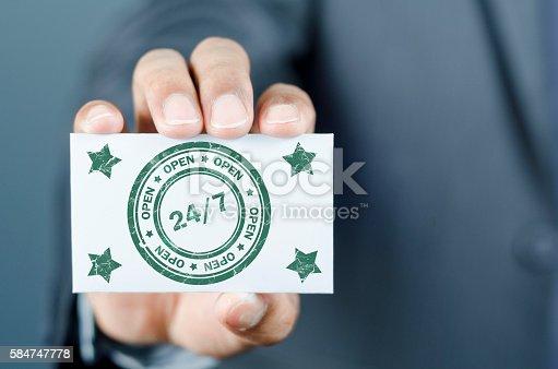 Man showing card indicating  24/7 service.