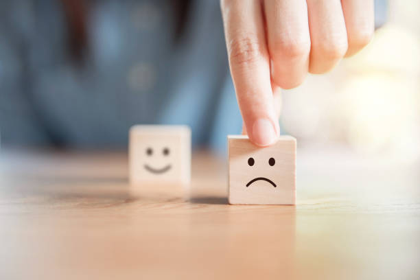 Service rating, satisfaction concept. Close up customer hand choose sad face and blurred smiley face icon on wood cube, Service rating, satisfaction concept. negative emotion stock pictures, royalty-free photos & images