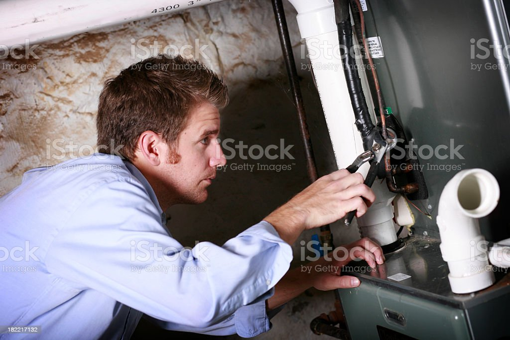 A service repairman works on furnace royalty-free stock photo