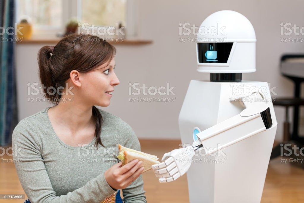 robot de servicio es dar a una mujer morena, bonita un sándwich en la sala de estar, pantalla del robot doméstico muestra un símbolo de pausa café - Foto de stock de Adulto libre de derechos