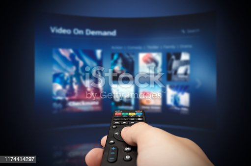 istock VOD service screen with remote control in hand 1174414297