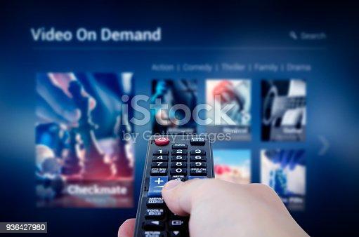 istock VOD service screen with remote control in hand 936427980