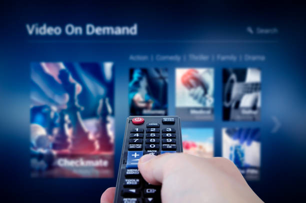 VOD service screen with remote control in hand stock photo
