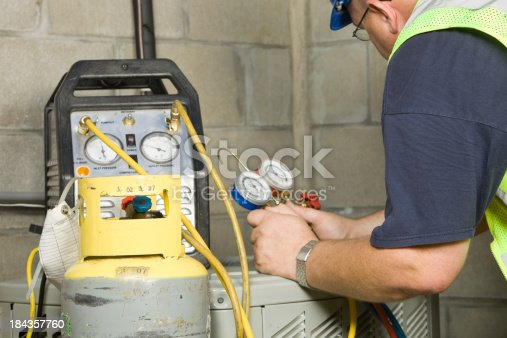 istock Service Technician Recovers Refrigerant from Air Conditioner System 184357760