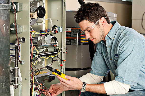 Service technician testing a furnace. Service technician testing a furnace technician stock pictures, royalty-free photos & images