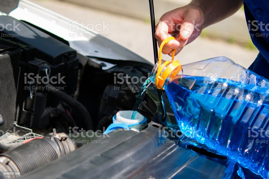 service worker, pours in the tank washer fluid for washing car windows stock photo