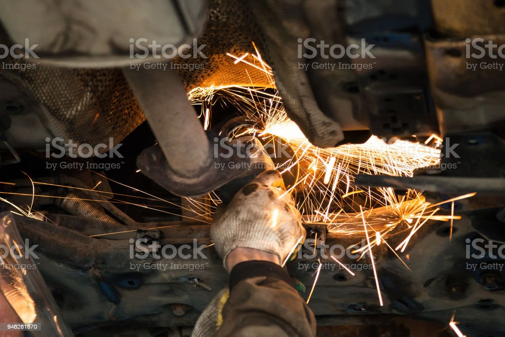 serviceman cleans muffler pipe by angle grinder stock photo