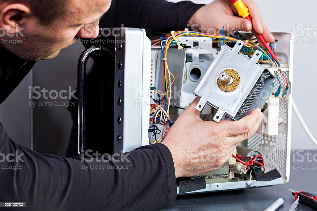 Serviceman electrician repairs a magnetron in the microwave stock photo