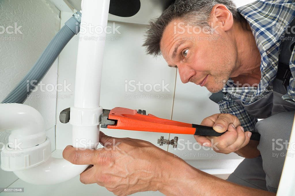 Serviceman Fixing Sink Pipe In Kitchen stock photo