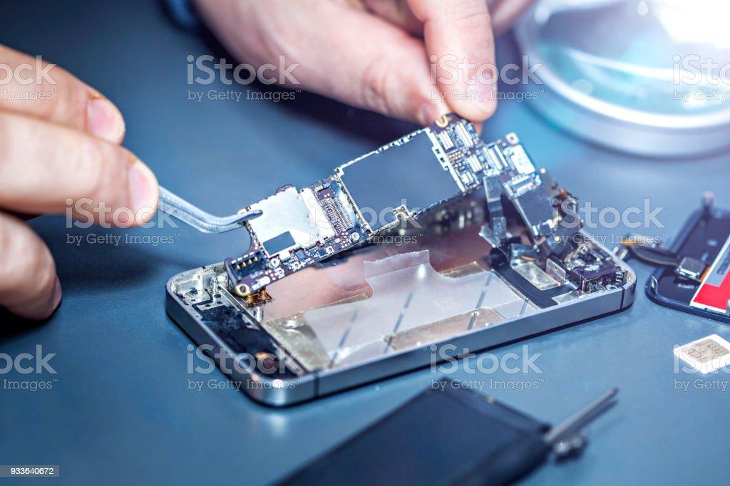 Soldat ist ein beschädigtes Handy Reparatur. – Foto