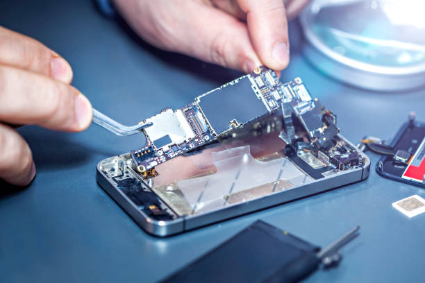 serviceman is repairing a damaged mobile phone. - broken iphone stock photos and pictures