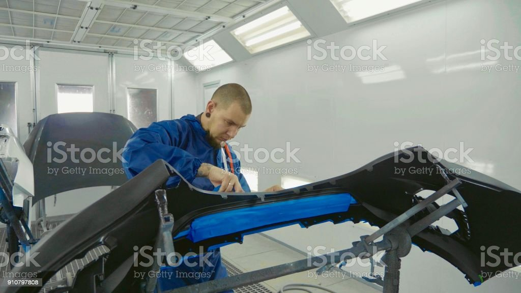 Serviceman preparing a car bodykit for painting in a workshop stock photo