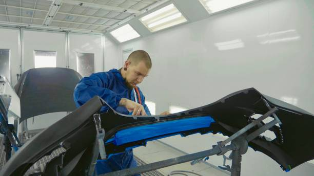 serviceman preparing a car bodykit for painting in a workshop - auto body repair stock photos and pictures