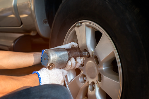 serviceman removing bolt from a wheel using pneumatic gun, tire replacement. Close up of mechanic changing wheel on car with pneumatic wrench