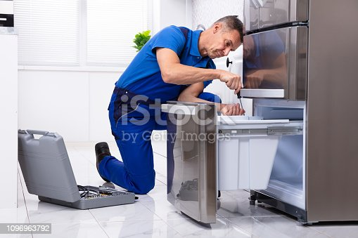 Mature Male Serviceman Repairing Refrigerator With Toolbox In  Kitchen