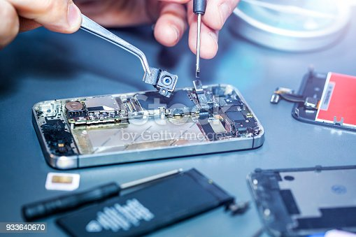 istock Serviceman repairs the damaged camera on the smartphone 933640670