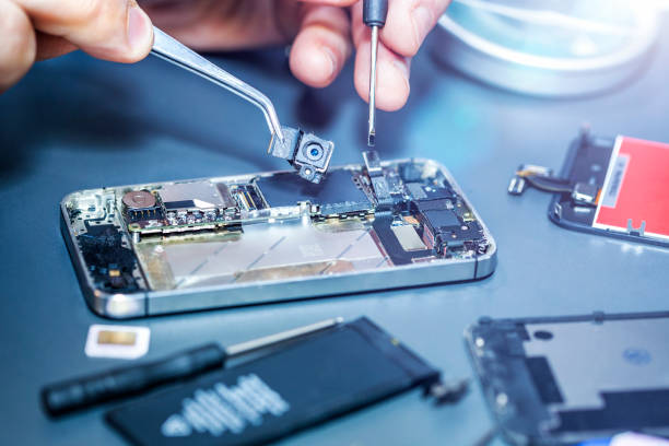 Serviceman repairs the damaged camera on the smartphone stock photo