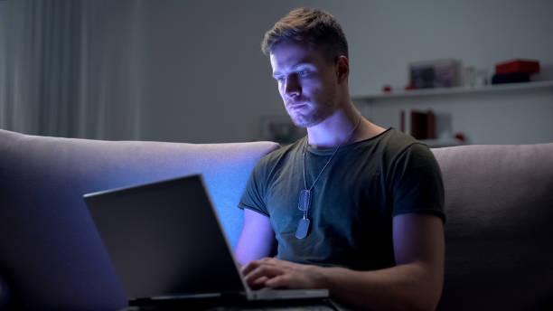 Serviceman searching job on laptop at home, adapting to civilian life after army Serviceman searching job on laptop at home, adapting to civilian life after army sergeant stock pictures, royalty-free photos & images