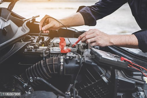 istock Services car engine machine concept, Automobile mechanic repairman hands checking a car engine automotive workshop with digital multimeter testing battery, car service and maintenance 1130307935