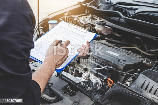 Services car engine machine concept, Automobile mechanic repairman checking a car engine with inspecting writing to the clipboard the checklist for repair machine, car service and maintenance.