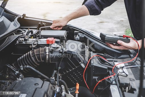 istock Services car engine machine concept, Automobile mechanic repairman hands repairing a car engine automotive workshop with a wrench and digital multimeter testing battery, car service and maintenance 1130307997