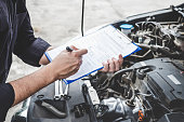 istock Services car engine machine concept, Automobile mechanic repairman checking a car engine with inspecting writing to the clipboard the checklist for repair machine, car service and maintenance 1130310297