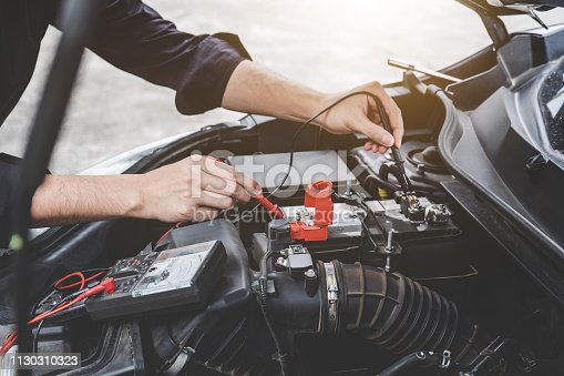 istock Services car engine machine concept, Automobile mechanic repairman hands checking a car engine automotive workshop with digital multimeter testing battery, car service and maintenance 1130310323