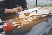 istock Services car engine machine concept, Automobile mechanic repairman checking a car engine with inspecting writing to the clipboard the checklist for repair machine, car service and maintenance 1131974019