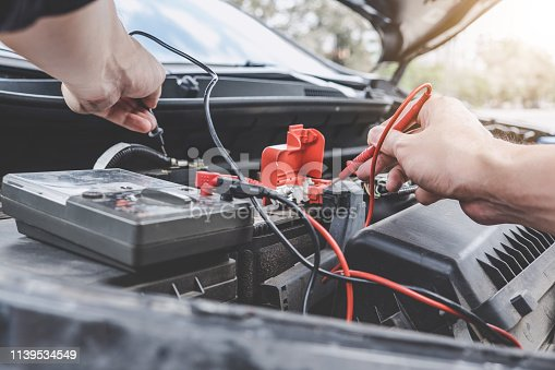 istock Services car engine machine concept, Automobile mechanic repairman hands checking a car engine automotive workshop with digital multimeter testing battery, car service and maintenance 1139534549