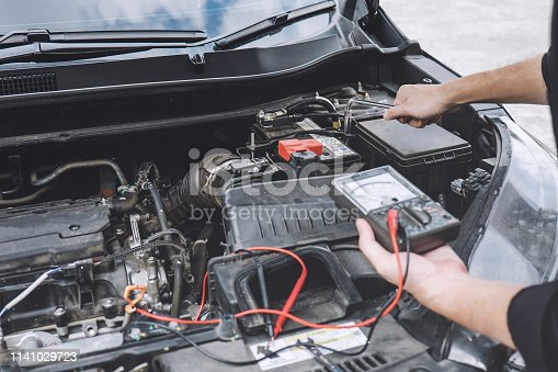 istock Services car engine machine concept, Automobile mechanic repairman hands repairing a car engine automotive workshop with a wrench and digital multimeter testing battery, car service and maintenance 1141029723