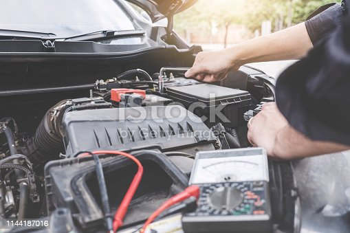 istock Services car engine machine concept, Automobile mechanic repairman hands repairing a car engine automotive workshop with a wrench and digital multimeter testing battery, car service and maintenance 1144187016