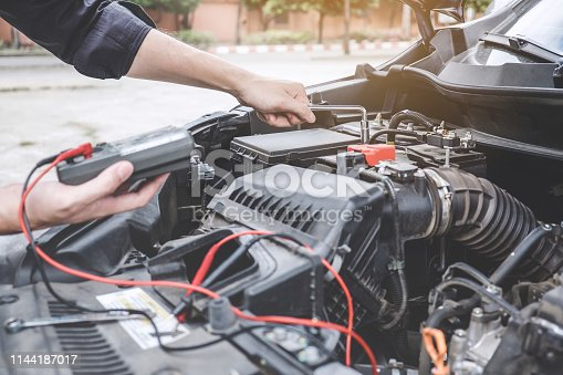istock Services car engine machine concept, Automobile mechanic repairman hands repairing a car engine automotive workshop with a wrench and digital multimeter testing battery, car service and maintenance 1144187017