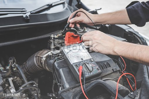istock Services car engine machine concept, Automobile mechanic repairman hands checking a car engine automotive workshop with digital multimeter testing battery, car service and maintenance 1144187021