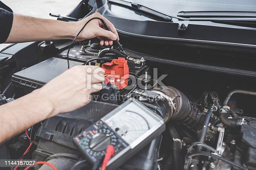 istock Services car engine machine concept, Automobile mechanic repairman hands checking a car engine automotive workshop with digital multimeter testing battery, car service and maintenance 1144187027