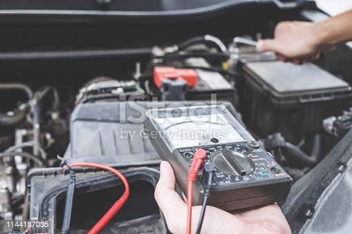 istock Services car engine machine concept, Automobile mechanic repairman hands repairing a car engine automotive workshop with a wrench and digital multimeter testing battery, car service and maintenance 1144187035