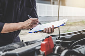 istock Services car engine machine concept, Automobile mechanic repairman checking a car engine with inspecting writing to the clipboard the checklist for repair machine, car service and maintenance 1168773208
