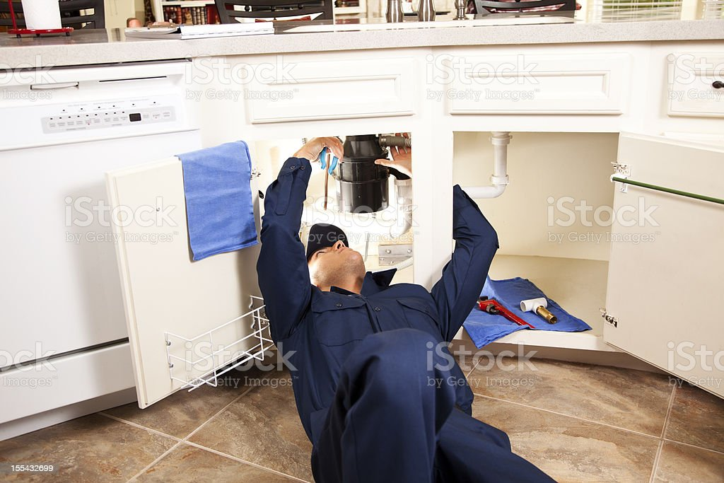 Services Industry:  Plumber working under sink in kitchen. royalty-free stock photo