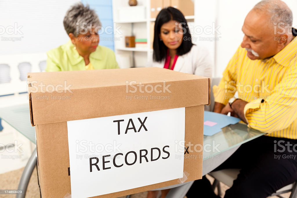 Services: Office accountants working on box of tax records royalty-free stock photo
