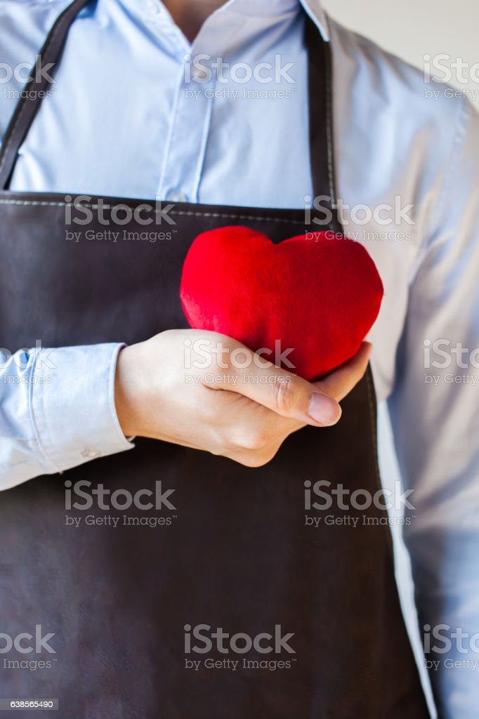 Servicing man in apron holding open armed heart with hands stock photo