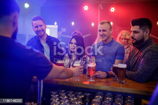 Bartender serving freshly draft beer to people at the bar counter in a pub