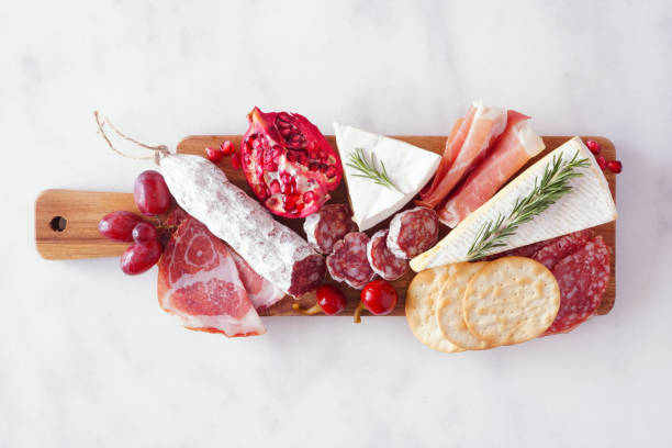 Serving board of assorted meats, cheeses and appetizers, top view on white marble stock photo