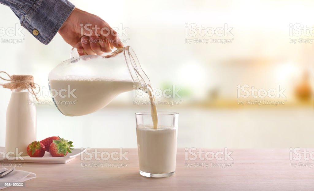 Desayunos leche con una jarra en un vaso sobre una mesa de cocina blanca de madera - foto de stock